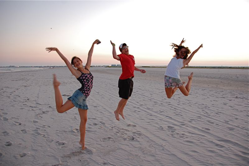 jumping for joy at sunset on the beach